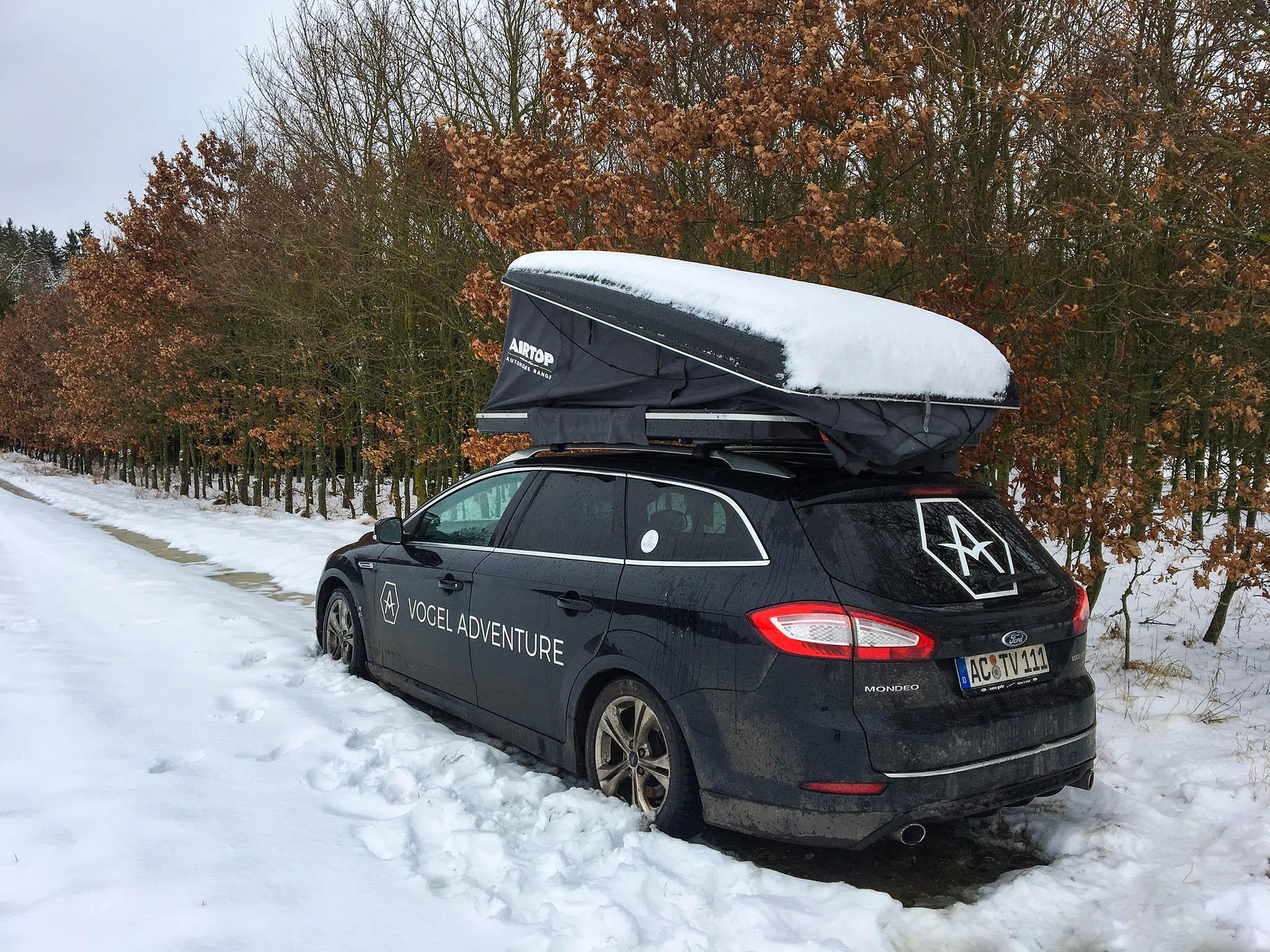 Ford Mondeo mir Dachzelt schneebedeckt. Eine Seite des Dachzeltes ist durch die Schneelast eingeknickt.