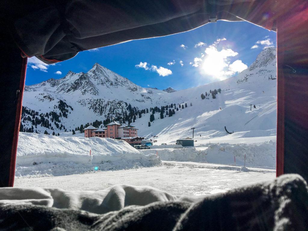 Dieses Bild zeigt die Aussicht aus einem  Dachzelt auf ein verschneites Tal in den Bergen.