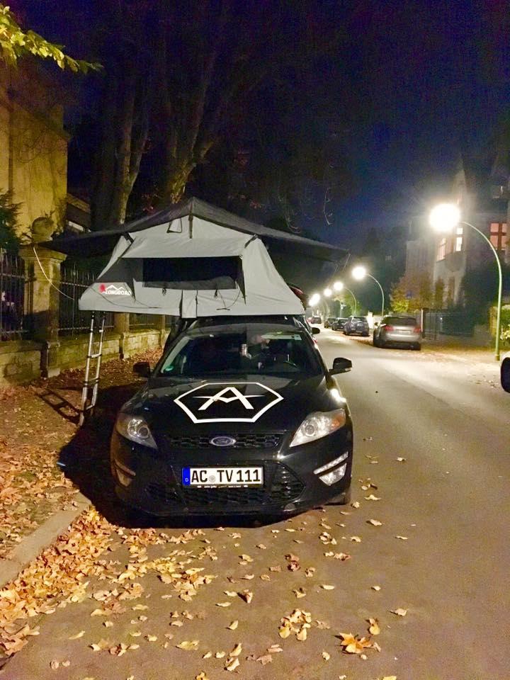 Vogeladventure campt in der Stadt mit Dachzelt auf dem Autodach