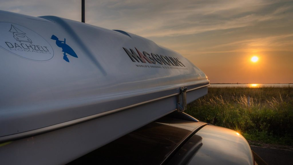 Auf dem Bild ist ein Dachzelt auf einem Auto vor Sonnenuntergang