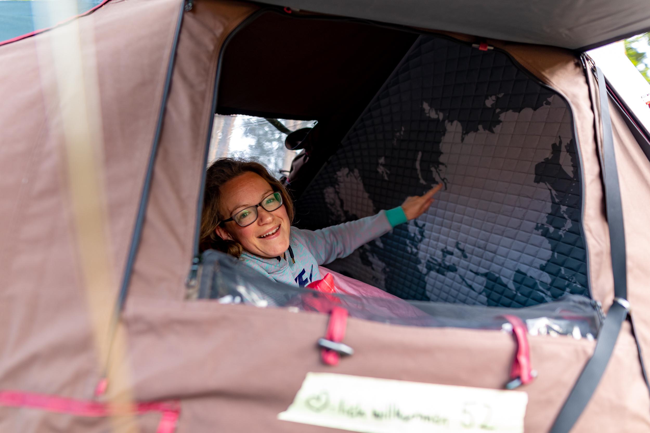 Frau mit Brille liegt im Dachzelt und zeigt auf Weltkarte.