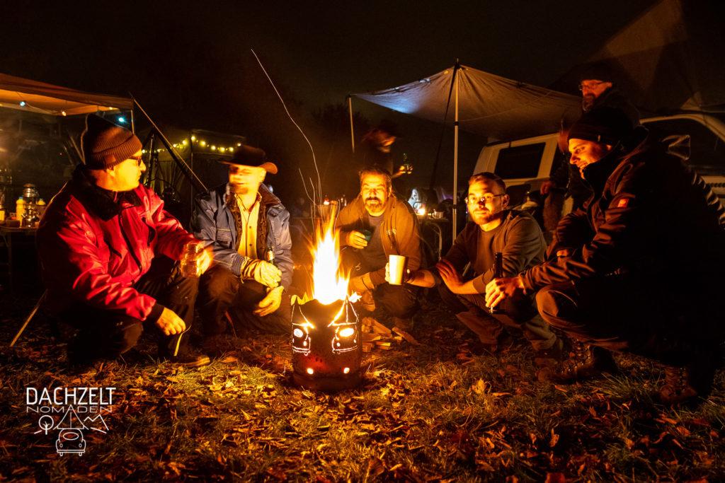 Diese Bild zeigt Menschen, die um ein Lagerfeuer sitzen