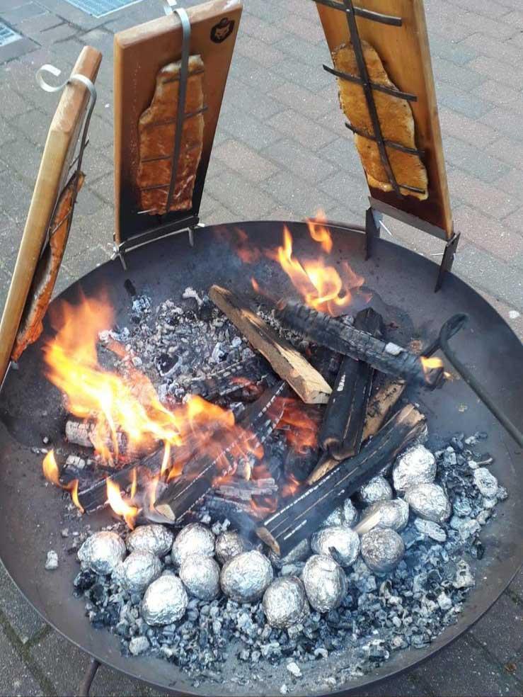 Dieses Bild zeigt Flammlachs auf Flammlachsbrettern am Feuer.