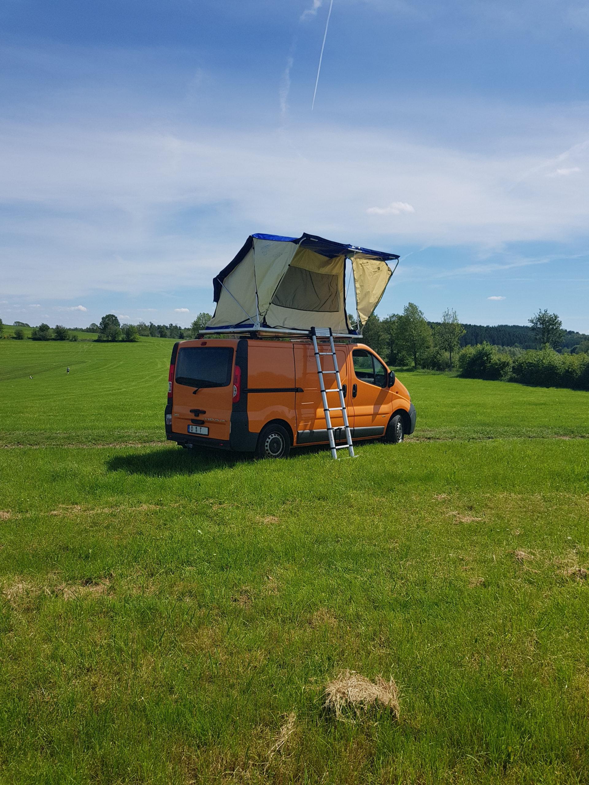 Selbst gebautes Dachzelt auf Transporter auf einer Wiese