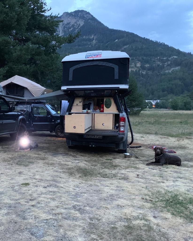 Hund liegt neben einem Ford Ranger mit Dachzelt
