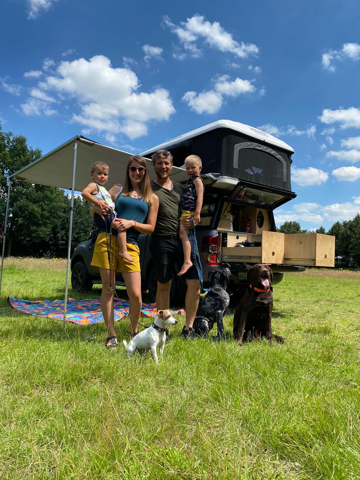 Familie mit zwei Kindern und drei Hunden vor einem Fahrzeug mit Dachzelt, Markise und ausgefahrenen Schubladen