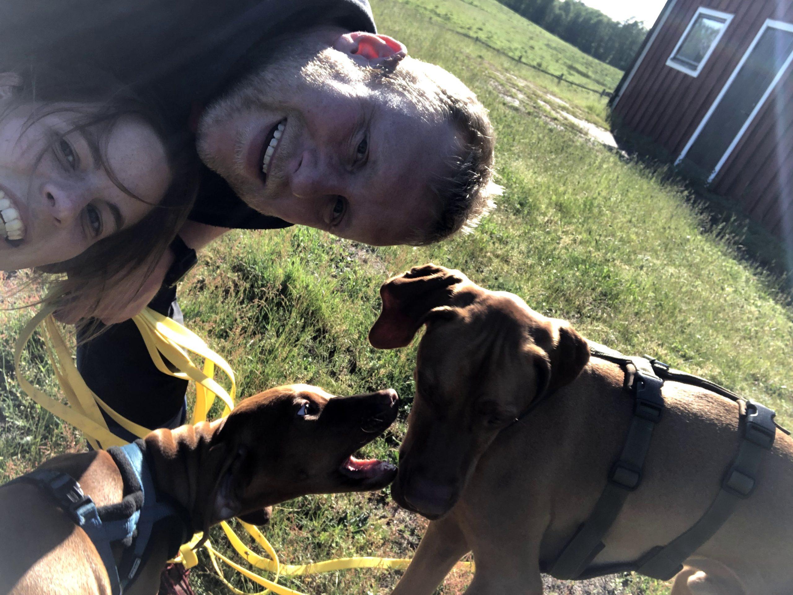 Menschen mit Hunden vor einem Schwedenhaus