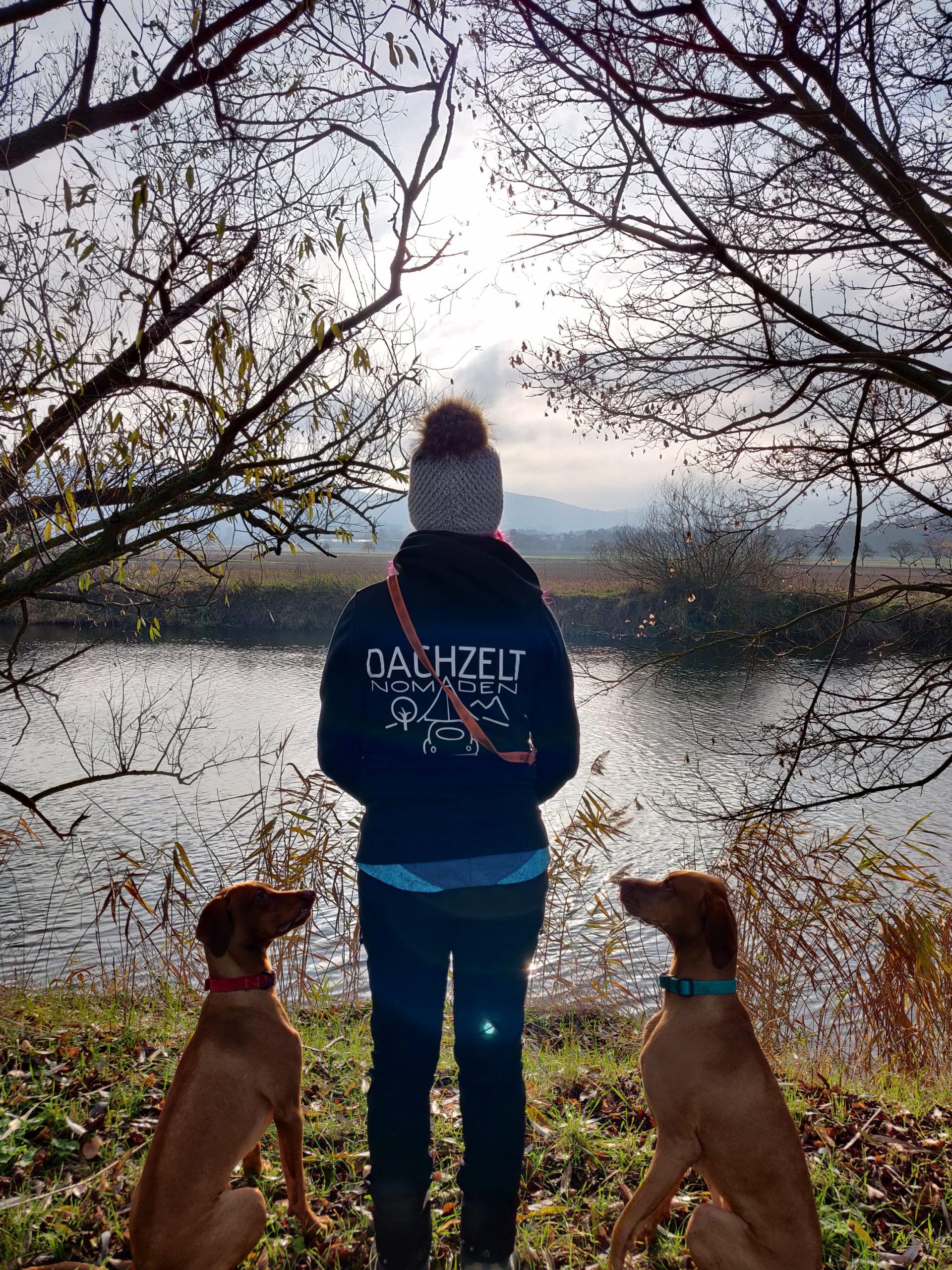 Frau steht mit zwei Hunden an einem Fluss und hat ein Dachzeltnomaden Hoodie an