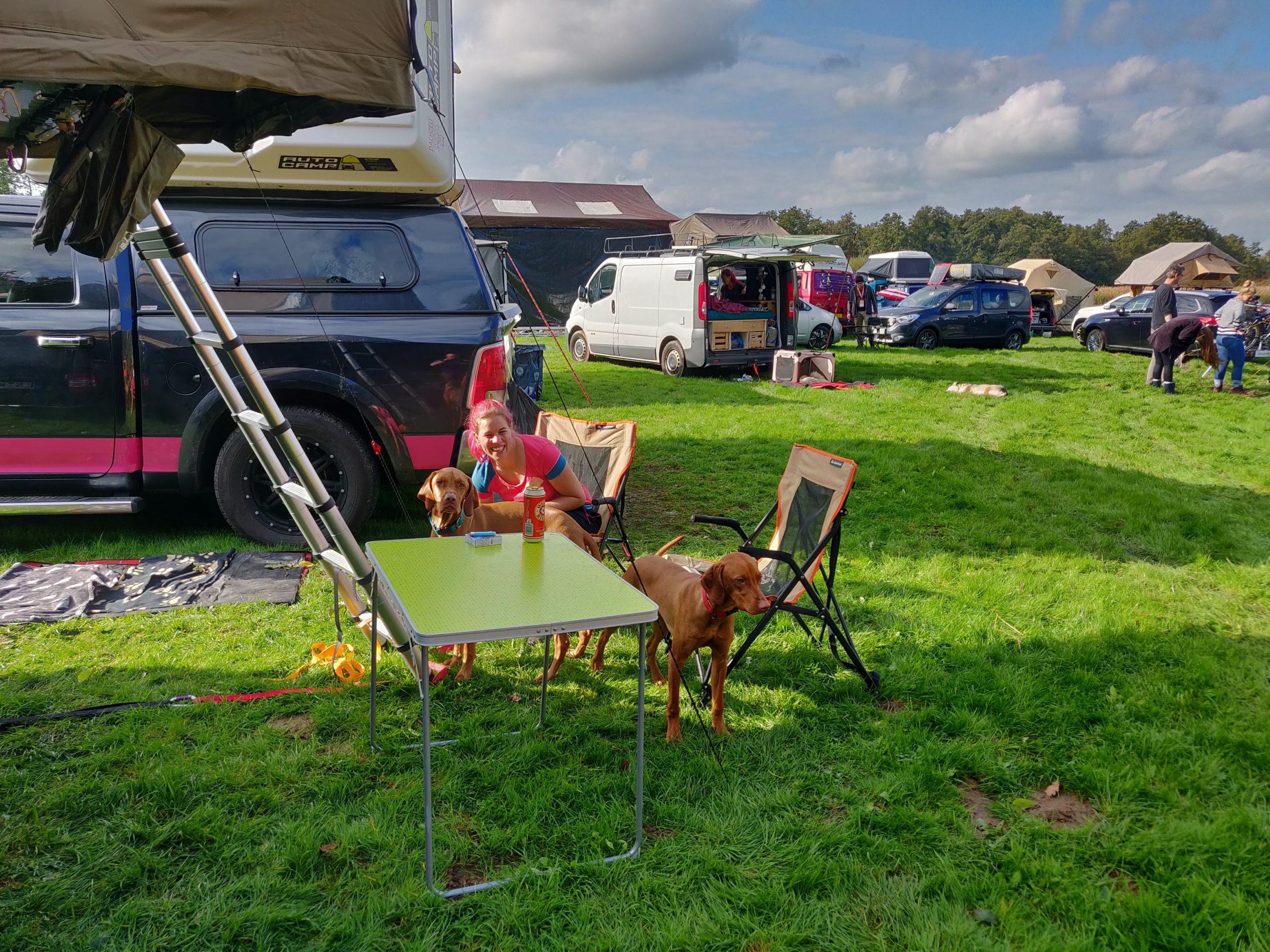 Dachzelte im Hintergrund und eine Frau mit zwei Hunden sitzt an einem Tisch und beobachtet etwas