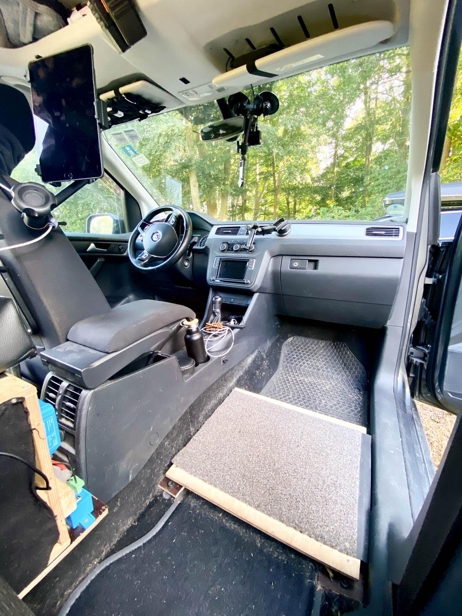 Ausgebauter Beifahrersitz in einem VW Caddy, die Halterungen sind mit einem Brett abgedeckt