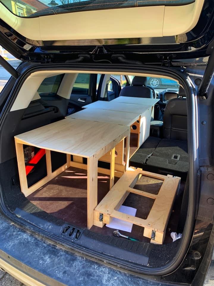 Sitze umgeklappt und eine Rahmenkonstuktion aus holz zum Campen