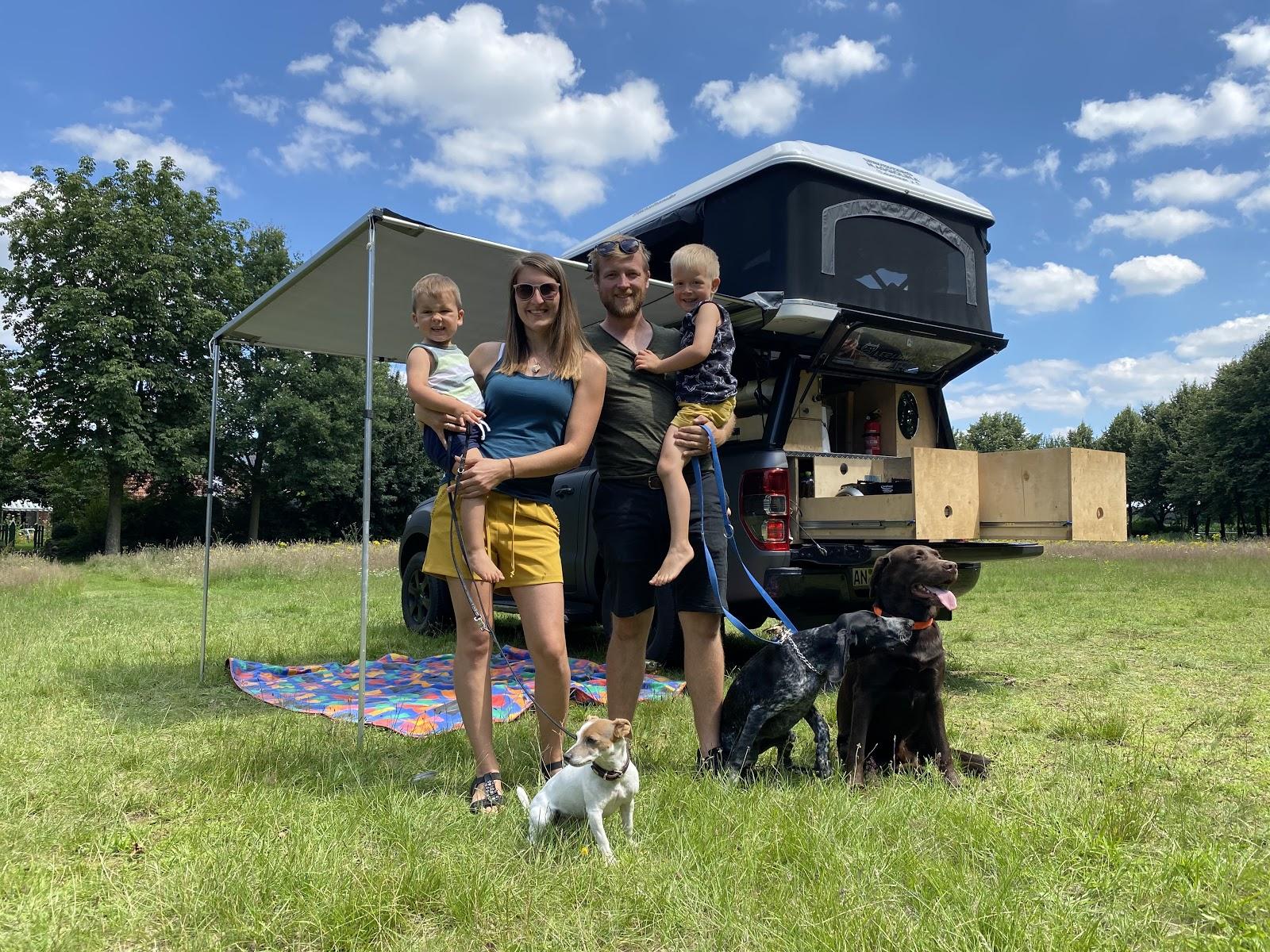 familie mit 2 Kindern und drei Hunden, im Hintergrunf ein Dachzelt mit Auto Ausbau und Markise
