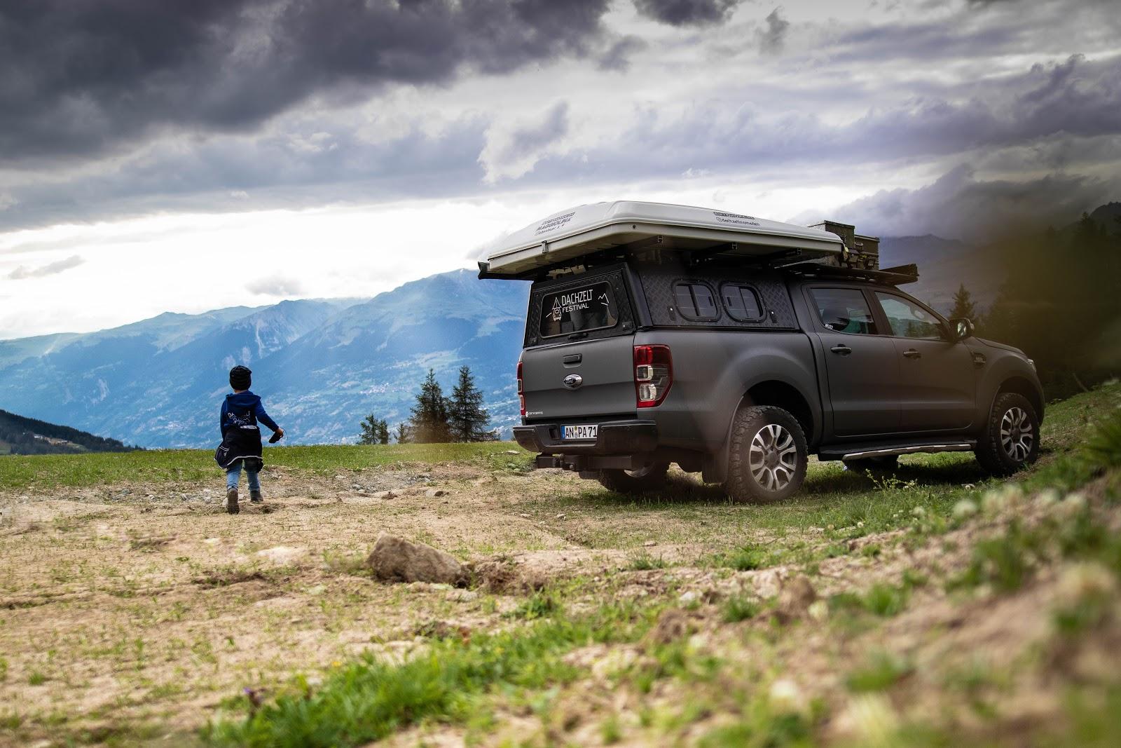 Kind in Natur vor Bergen, neben Ford Ranger mit Dachzelt