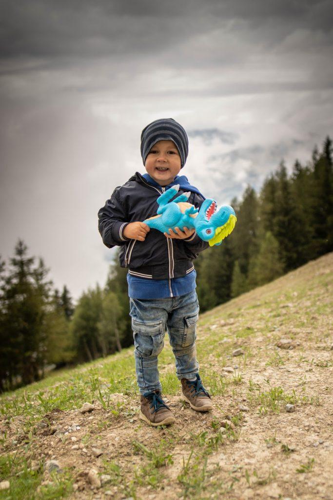 Junge hält Dinosaurier in der Hand und freut sich
