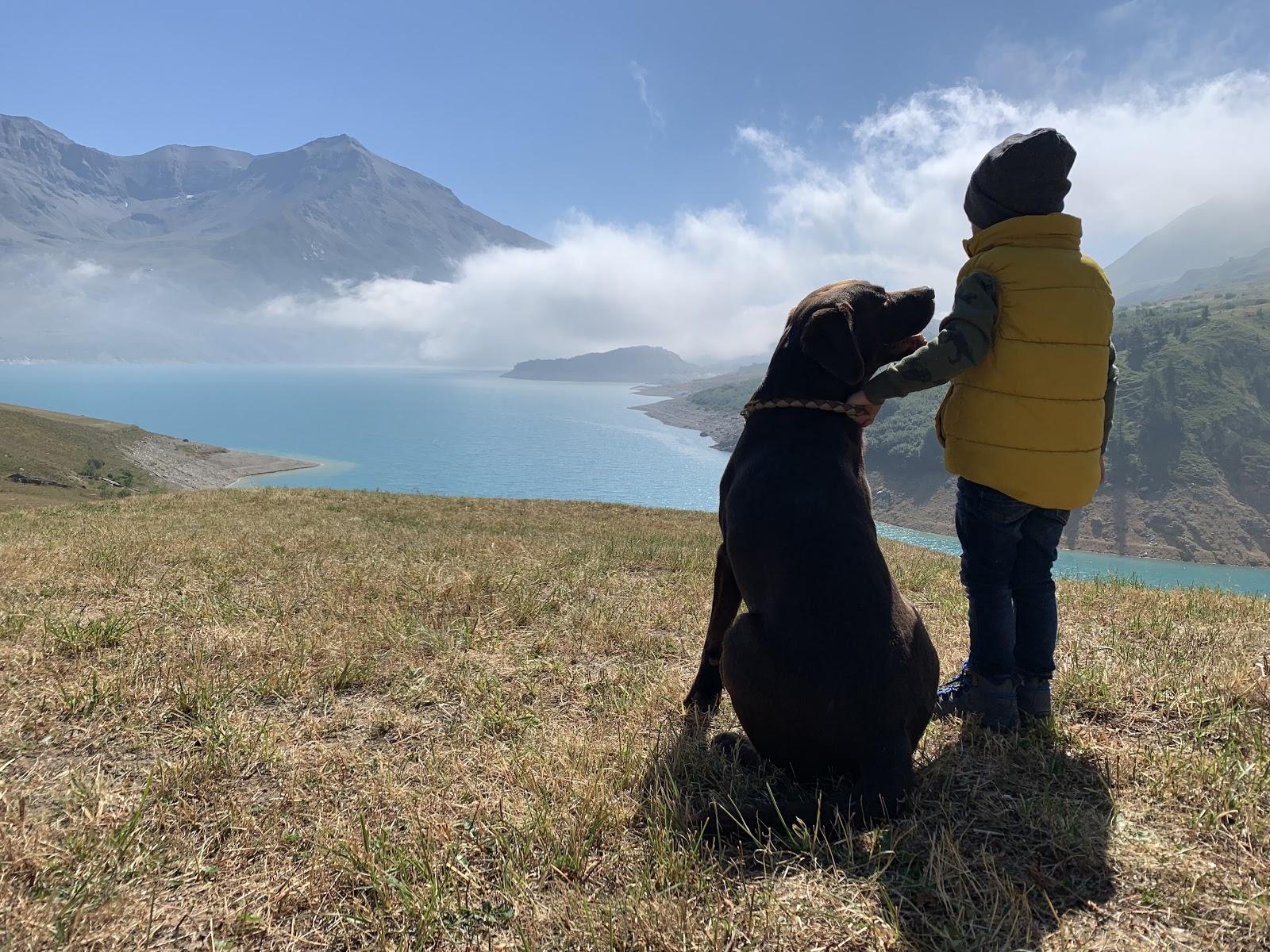 Junge steht mit Hund in der Natur und blickt auf Stausee