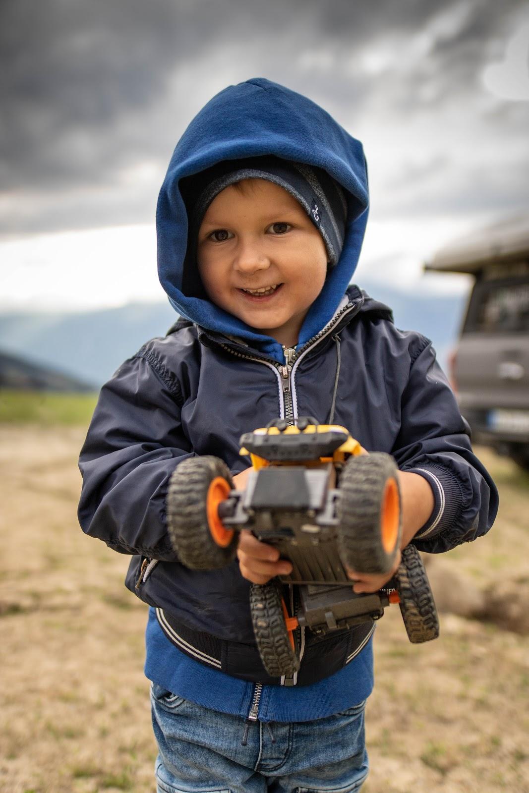 Junge lächelt in die Kamera mit Bagger in der Hand