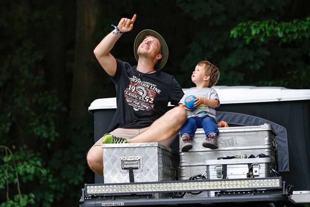 Papa sitzt mit Junge auf Dachbox und zeigt in den Himmel