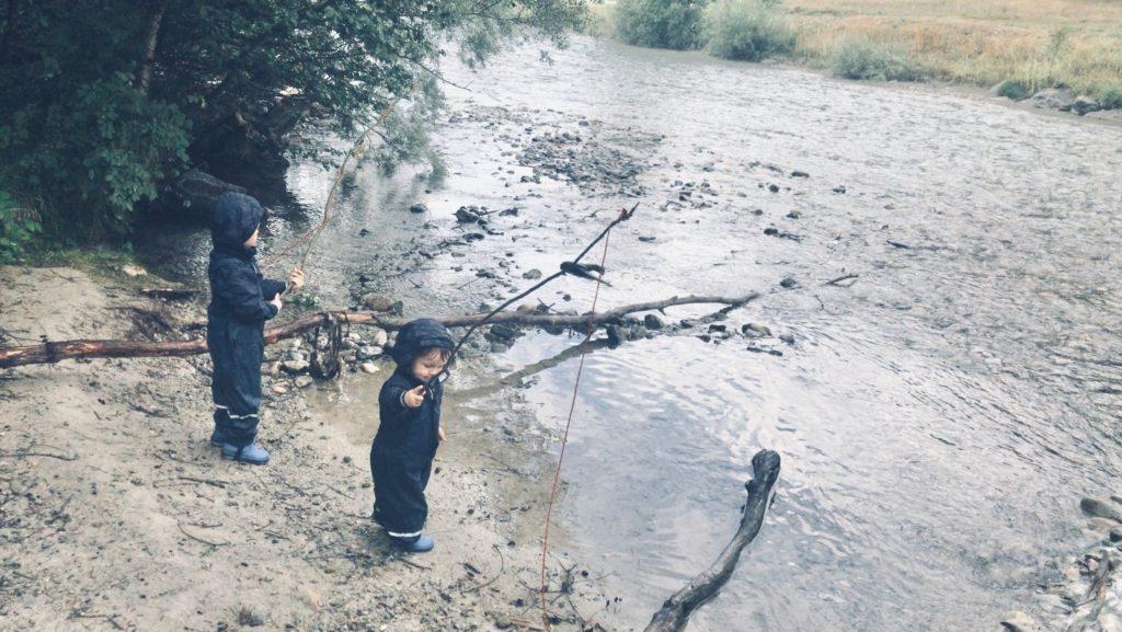 Kinder stehen am Wasser mit selbstgebastelten Angeln