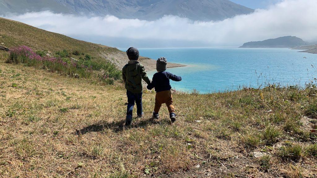 Kinder halten sich an der Hand und blicken auf Stausee