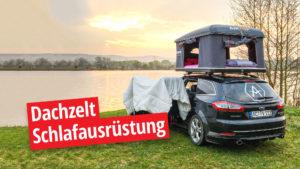 Auto mit Dachzelt und Schlafausrüstung vor See und Sonnenuntergang