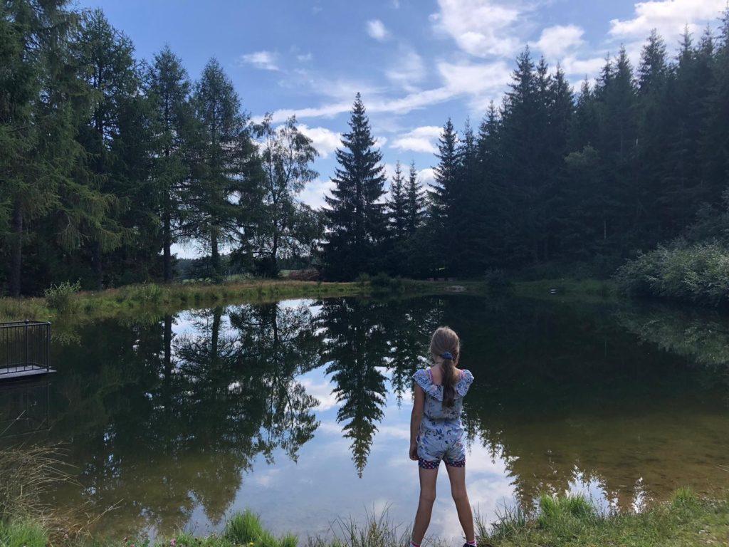 Kind steht vor See und genießt den Ausblick